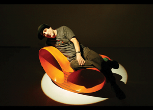 Ron Arad, wearing his trademark Cappellone, on an orange Oh-Void chair.