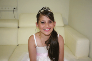 A smiling Shefa Shukrun in her bat mitzva dress. courtesy of Yael Halfon.