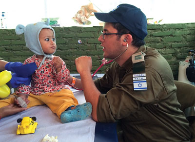 Hadassah pediatrician Dr. Uri Ilan interacts with a young Nepalese patient at The State of Israel IDF Medical Corps Hospital.