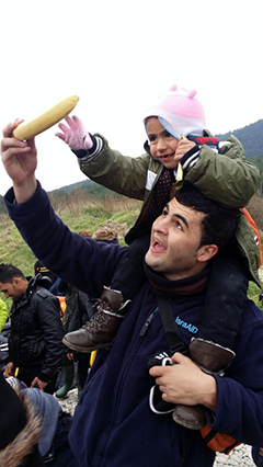 Paramedic Molham Zreqe with a two-your-old Syrian girl on the shores of Lesbos, near Mytilini.